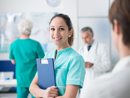 Young female medical student working at the hospital and medical staff, she is holding medical records Standard-Bild