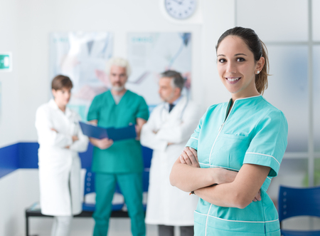 Young nurse posing at the clinic with arms crossed and medical team working on the background Stockfoto