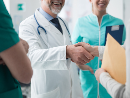 Smiling confident doctor shaking patients hand at the hospital and medical staff