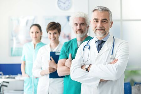 Medical team standing in line at the hospital and smiling at camera, healthcare and medical occupations concept Stok Fotoğraf