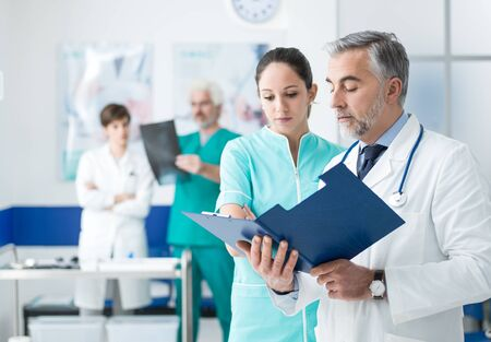 Doctor and nurse examining patient's medical records and medical team working on the background Stock Photo