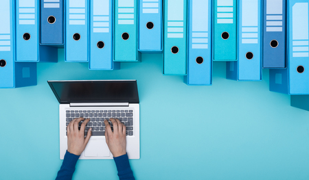 Organized archive with ring binders and woman searching for files in the database using a laptop, top view 版權商用圖片 - 96977399