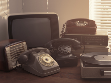 Vintage retro revival objects and second-hand appliances collection on a table: record player, television, radio and rotary dial telephones 写真素材