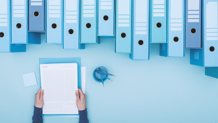 Office worker reading paperwork and archive binders, files database and management concept, top view Stock Photo