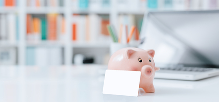 Piggy bank and credit card on a office desktop: savings, investments and bank deposit concept