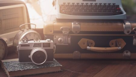 Vintage objects on a desk: suitcase, camera, radio, typewriter and alarm clocks