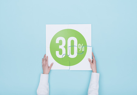 Woman completing a puzzle with a 30% off discount icon, she is putting the missing piece, shopping and discounts concept