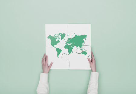 Woman completing a puzzle with a world map, she is putting the missing piece, globalization concept Stock Photo