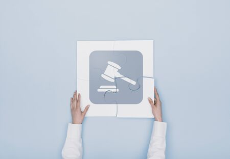 Woman completing a puzzle with a gavel icon, she is putting the missing piece, justice and law concept Stock Photo