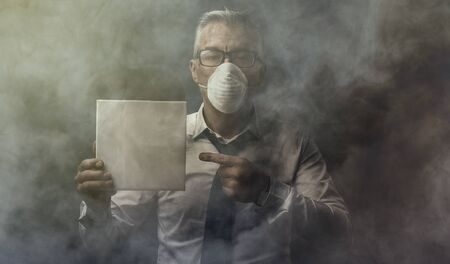Businessman wearing a mask and polluted air, he is holding a blank sign, environmental care and pollution concept
