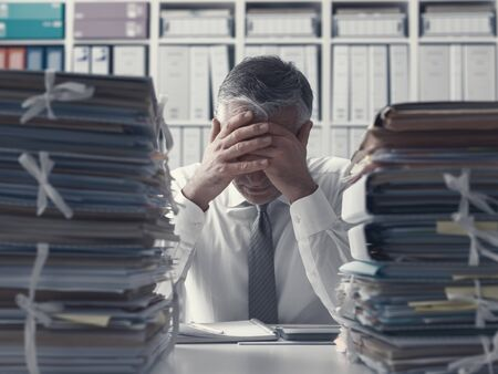 Stressed exhausted business executive in the office overloaded with work, he has stacks of paperwork on the desk