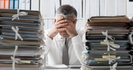Stressed exhausted business executive in the office overloaded with work, he has piles of paperwork on the desk
