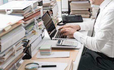 Der Unternehmensleiter, der im Büro und in den Stapel der Schreibarbeit arbeitet, schließt an einen Laptop an und schreibt