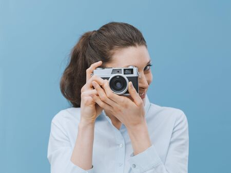 Young attractive woman holding a vintage camera and shooting pictures