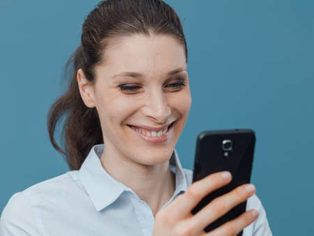 Smiling young woman connecting with her smartphone and social networking Stock Photo