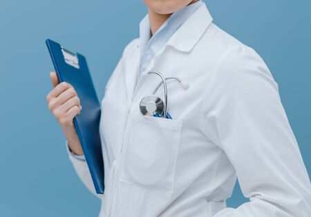 Professional female doctor holding a clipboard and posing, healthcare professionals concept