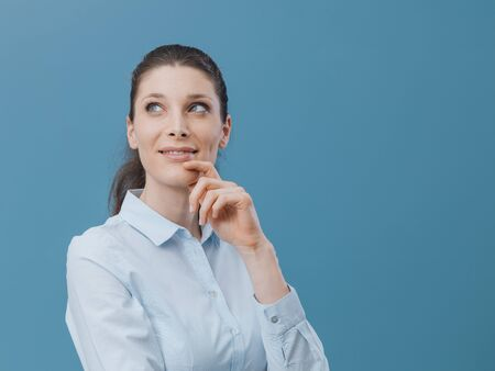 Confident attractive woman posing with hand on chin, she is thinking and looking away