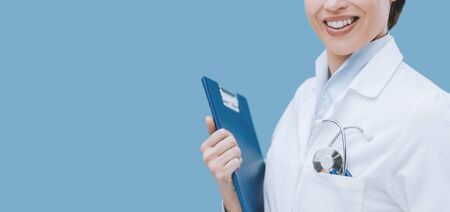 Smiling female doctor holding a clipboard and posing, healthcare professionals Stock Photo