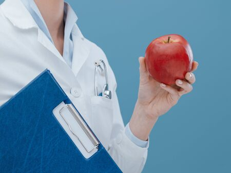 Professional nutritionist holding an apple, diet and healthcare concept