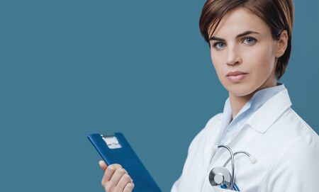 Confident female doctor holding a clipboard and looking at camera Stock Photo