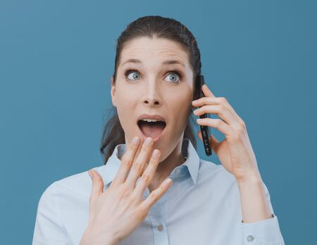 Surprised young woman having a phone call with her smartphone, she is receiving shocking news