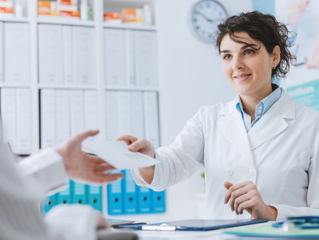 Doctor and patient meeting in the office, the doctor is giving a prescription and a medical report to a woman Stock Photo