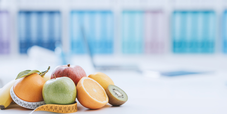 Fresh healthy fruits and tape measure in the nutritionist office: dieting and weight loss concept Stock Photo