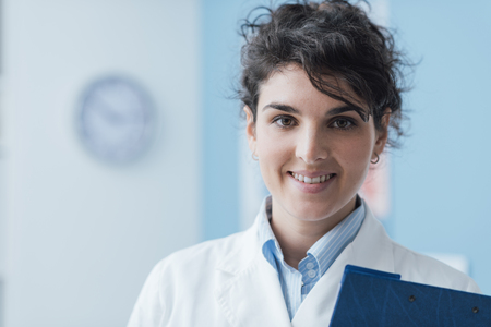 Smiling professional young doctor posing in the office and looking at camera, she is holding a clipboard