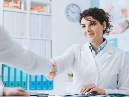Smiling female doctor greeting a patient and shaking hands, they are having a meeting in the office