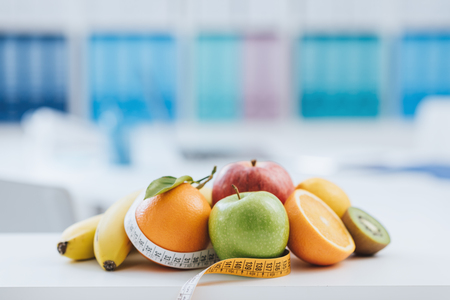 Fresh healthy fruits and tape measure in the nutritionist office: dieting and weight loss concept Zdjęcie Seryjne