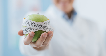 Professional nutritionist holding a fresh apple with tape measure: diet and weight loss concept