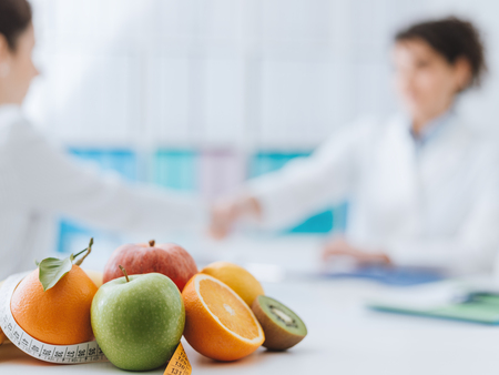 Professional nutritionist meeting a patient in the office and healthy fruits with tape measure on the foreground: healthy eating and diet concept Stock Photo