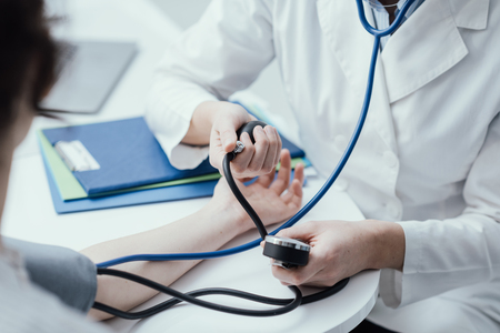 Doctor visiting a patient and checking her blood pressure at the hospital, healthcare and medical examination concept