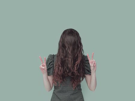 Funny portrait of a shy woman hiding her face behind her hair and making V signs