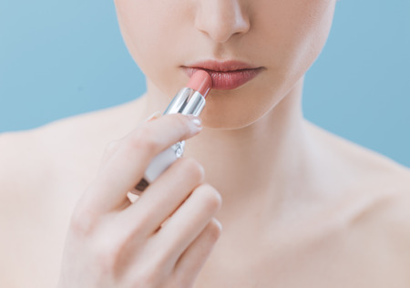 Young beautiful woman applying a pink lipstick on her lips, skin care and make-up concept