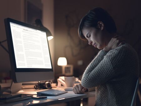 Young woman working with her computer late in the office and suffering from neck pain