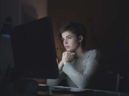 Young woman connecting late at night and watching videos online, she is staring at the computer screen