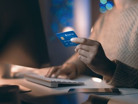Woman connecting with her computer late at night and doing online shopping, she is entering credit card information, hands close up