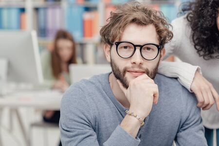 Young smiling hipster man sitting at desk, his colleague is leaning on his shoulder, office interior on the background Stock Photo