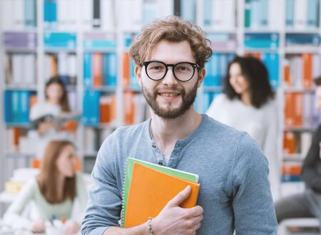 Hipster university student holding notebooks and smiling, students on the background