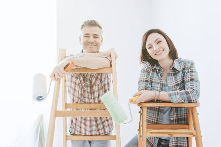 Happy couple painting their home, they are standing on a ladder, holding a paint roller and smiling