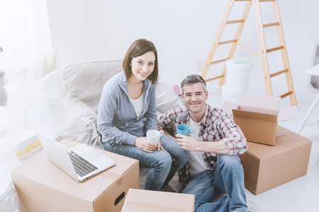 Couple moving in together, they are renovating their new house, unpacking boxes and connecting with a laptop