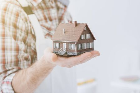 Building contractor holding a model house: construction, renovation and real estate concept Stock Photo