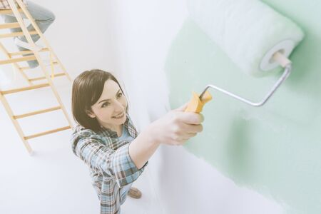 Smiling woman painting a room, she is applying a bright green color using a paint roller Stock Photo