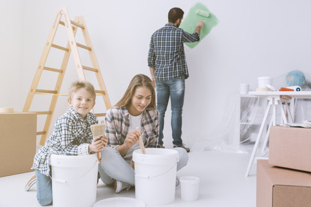 Young family doing a home makeover and painting rooms, the father is painting walls with a paint roller, the mother and her son are stirring paint in a bucket
