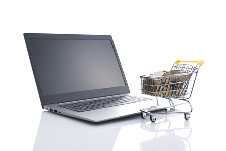 Shopping cart full of money and laptop: e-commerce, online banking and e-payments concept, white background Stock Photo