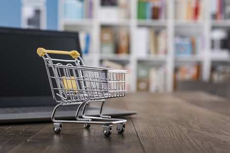 Miniature shopping cart and laptop on a desk: online shopping and e-commerce concept