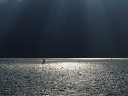 Lake with dramatic lighting and windsurfers, outdoors and nature concept