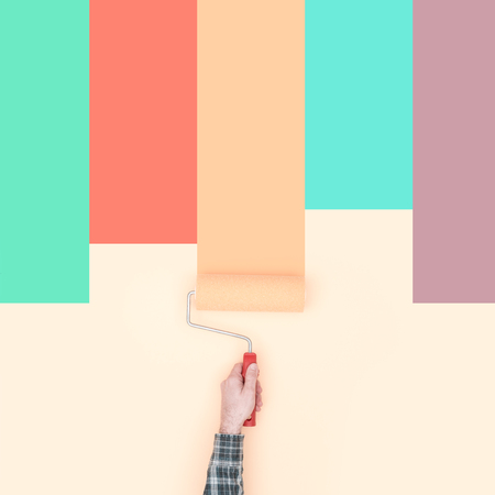 Decorator painting colorful stripes on a wall using a paint roller, creativity and do it yourself concept