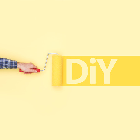 Decorator writing DIY on a wall using a paint roller, creativity and do it yourself concept Stock Photo